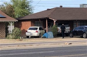 Woman shot and killed after car crashes into Phoenix home